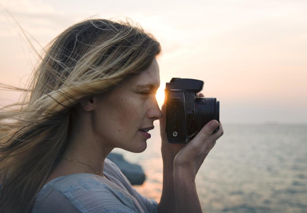Une fille qui prend une photo sur la plage