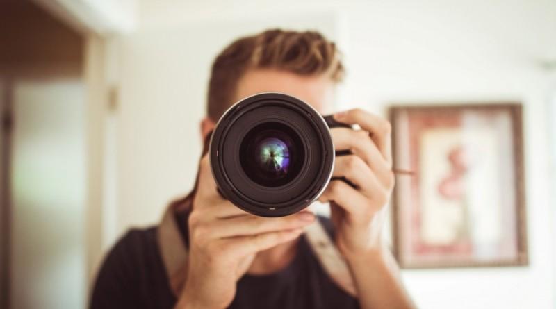 Homme qui pointe l'objectif d'un appareil photo.